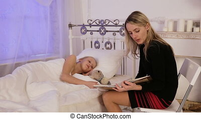 Mother and child reading book in dark bedroom