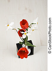 Top view of spring flowers in a vase on laminate flooring