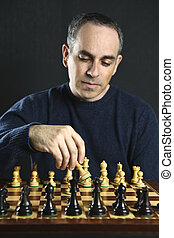 Man playing chess - Man moving a chess piece on wooden...