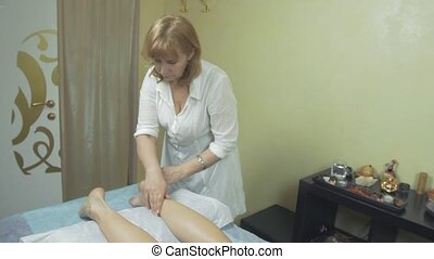 Masseuse make relaxing massage of left feet to young woman in saloon. Stroking