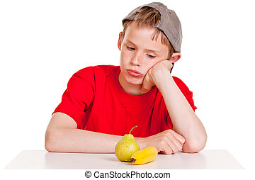Morose young boy staring at a ripe banana and pear - Morose...