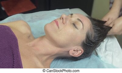 Masseuse make massage of head to woman in professional...
