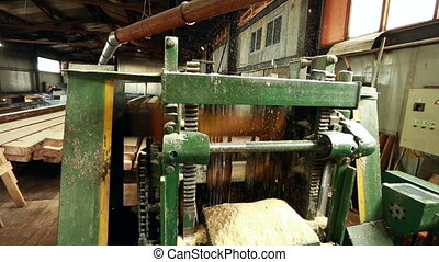 Close-up of machine running and flying shavings - Sawmill...