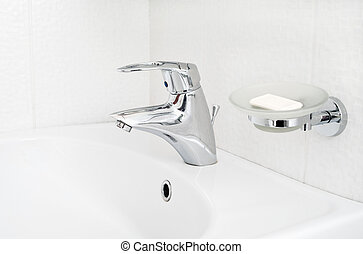 One chrome faucet in washbowl in bath room o white pile with soap holder