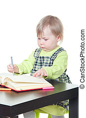 The little girl sits at a table and does a homework, draws in a notebook. It is isolated on a white background