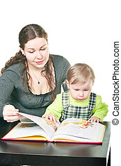 Little child and mother together read the book at a table. It is isolated on a white background