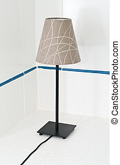 Electric table lamp on white tile background