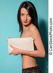Fashion studio photo of elegant nude woman with clutch