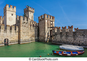 Scaliger medieval castle in Sirmione. - Boats on Lake Garda...