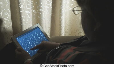 Woman working on digital tablet at home