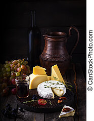 Cheese plate,grape and wine. Still life in rustic style.