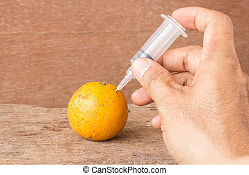 Hand with syringe and tangerine on wooden table
