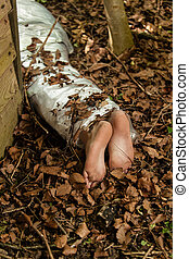 Wrapped barefoot corpse lying in the woods concealed behind...