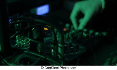Hands of DJ tweak various track controls on dj's deck