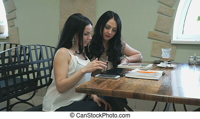 Two girls looking at pictures on electronic tablet - Two...