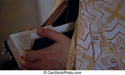 The priest turns the pages of the Bible - The priest turns...