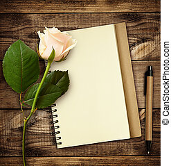 White rose flower with notebook and pen