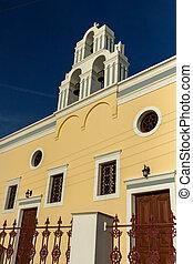 Sunset over yellow church, Fira, Santorini island, Thira,...
