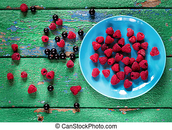 Summer berries on blue plate on old rustic painted cracky...