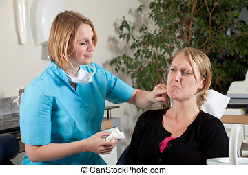 At the dentist - Female dentist touching the sore area on...