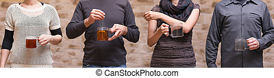four people with teaglasses are sharing a teabag, concept...
