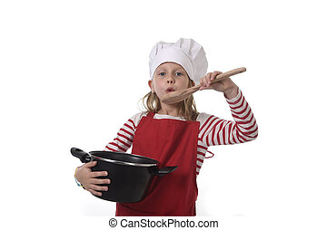 little girl in cooking hat and red apron playing cook...
