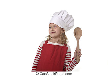 7 years old little girl in cooking hat and red apron playing...