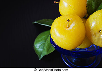 Organic ripe yellow plums in a glass bowl on a black wooden...