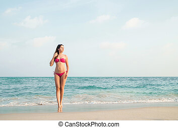 Hot girl wearing pink bikini on the summer beach -...