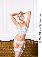 Beautiful young woman in bridal lingerie on a retro sofa -...