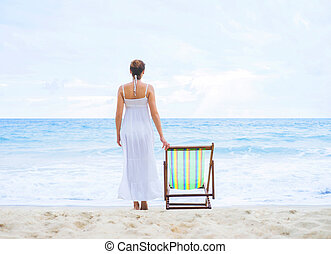 Beautiful woman in a white dress on the beach