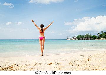 Beautiful woman in alluring pink bikini with hot legs and...
