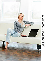 Young woman resting on sofa at home and drinking coffee -...