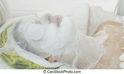 Woman face with clay mask covered by cheesecloth in beauty...