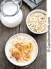 Breakfast oatmeal with banana and cinnamon, jug of milk,...