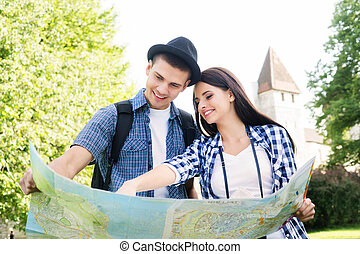 Traveling couple searching for their next destination with a...