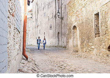 Young travelling couple having a walk on an old street with...