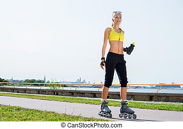 Young, beautiful, sporty and fit girl rollerblading on...