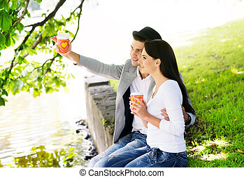 Couple sitting together on the riverside and drinking coffee...