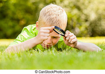 Child using magnifying glass - Single male child in blond...