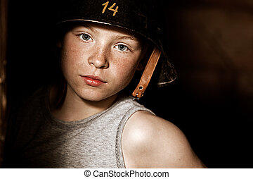 Serious little boy in army helmet