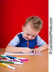 Small boy draws at the table On a red background
