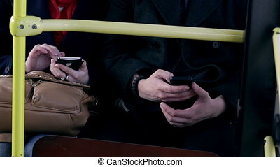 Young couple sit together on a bus and use smartphones