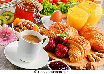 Breakfast consisting of croissants, coffee, fruits, orange...