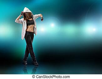 Girl dancer wearing hoodie stands on tiptoe raising her hands