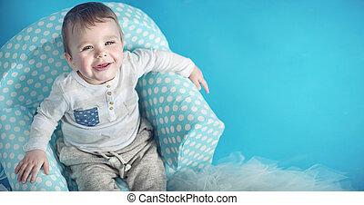 Joyful little man sitting on the comfortable armchair -...