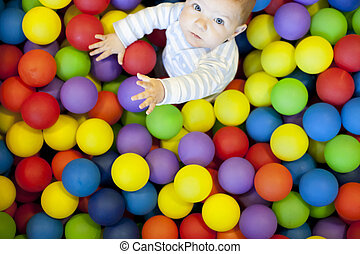baby boy playing in the playground balls pool
