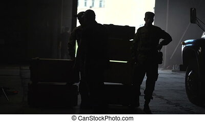 Silhouette of people in the hangar on the background of the boxes