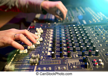 Professional audio mixing console with faders and adjusting...
