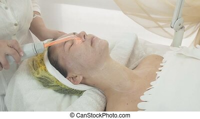 Cosmetologist use darsonval on woman face in beauty saloon...